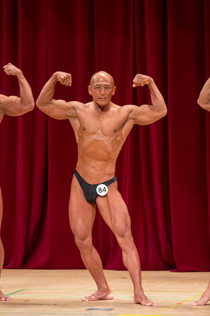 Japanese bulky bald head male 50s bodybuider posing front double biceps