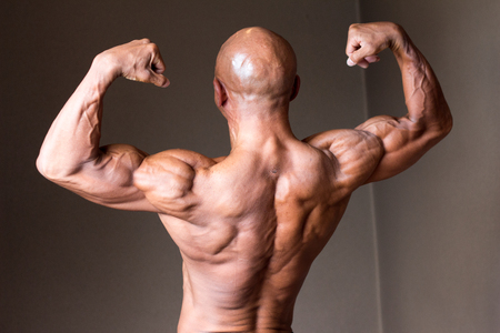 Japanese bulky bald head male 50s bodybuider posing back double biceps Stock Photo