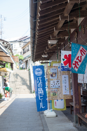 KANAGAWA, JAPAN - JULY 22, 2018: The entrance of the Enoshima shopping street in summer early morning: The gate of Enoshima shrine in summer early morning: The Enoshima shopping street with some eating and drinking advertising shop curtains in summer earl Editorial