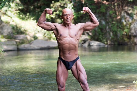 Japanese bald head bodybuilder posing the front double biceps at the river in summer