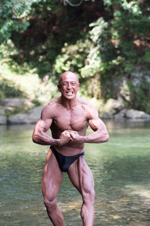 Japanese bald head bodybuilder posing the most musclure at the river in summer