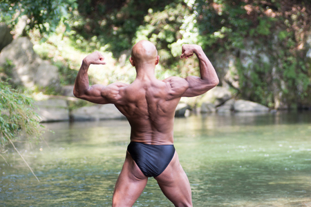 Japanese bald head bodybuilder posing the back double biceps at the river in summer