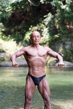 Japanese bald head bodybuilder posing the front relax at the river in summer