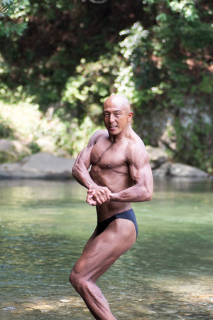 Japanese bald head bodybuilder posing the side chest at the river in summer Stock Photo