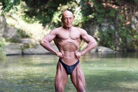 Japanese bald head bodybuilder posing the front lat spread at the river in summer