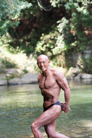 Japanese bald head bodybuilder posing the side triceps at the river in summer Stock Photo