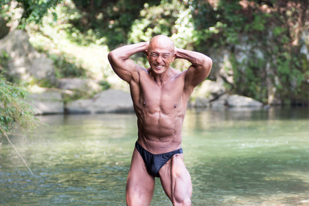 Japanese bald head bodybuilder posing the abdominal and thigh at the river in summer