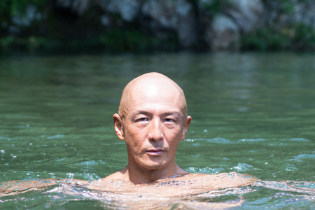 Blunt Japanese bald head guy soaked in the river