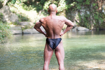 Japanese bald head bodybuilder posing the back lat spread at the river in summer