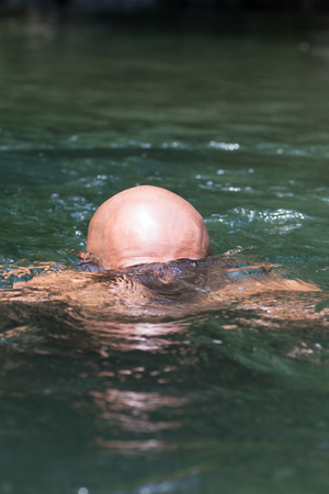 Japanese bald head guy emerging from water