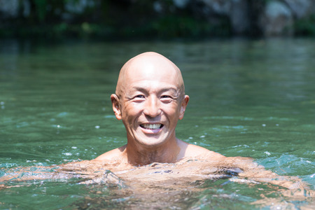 Smiling Japanese bald head guy soaked in water
