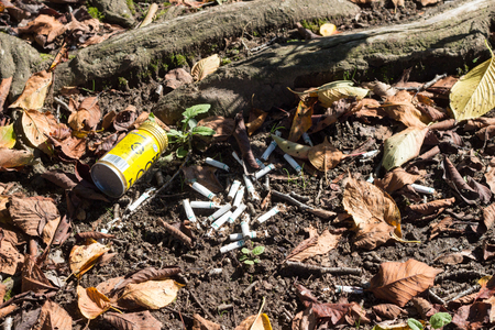 TOCHIGI, JAPAN – SEPTEMBER 19, 2018: The pile of litter cigarette butts and empty canned coffee on the ground in park Editorial