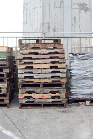 Piled old wooden pallets at harbor