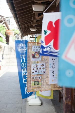 KANAGAWA, JAPAN - JULY 22, 2018: The entrance of the Enoshima shopping street in summer early morning: The gate of Enoshima shrine in summer early morning: The Enoshima shopping street with some eatin 報道画像
