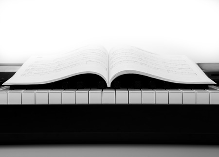 black and white keys of the piano closeup and musical book photo
