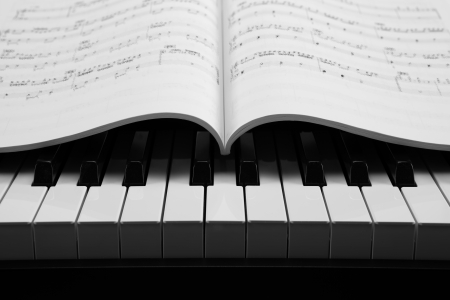 black and white keys of the piano closeup and musical book
