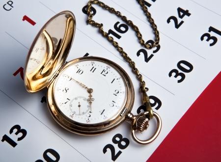 Gold pocket watch with wall calendar close-up
