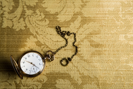 dispositions: Gold pocket watch on on gold cloth close-up Stock Photo