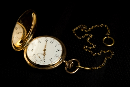 dispositions: Gold pocket watch on on black cloth close-up Stock Photo