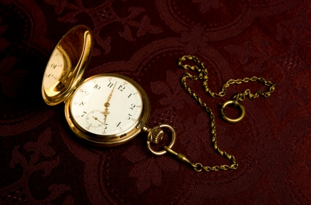 dispositions: Gold pocket watch on on maroon cloth close-up