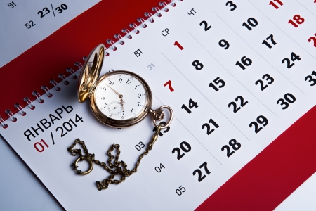 dispositions: Gold pocket watch with wall calendar close-up