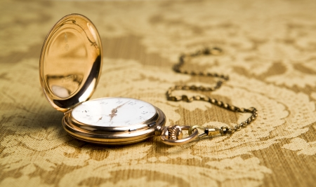 dispositions: Gold pocket watch on on gold tablecloth close-up