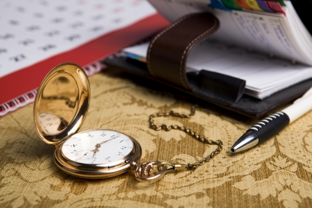 dispositions: Gold pocket watch with wall calendar and sketchpad, pen close-up