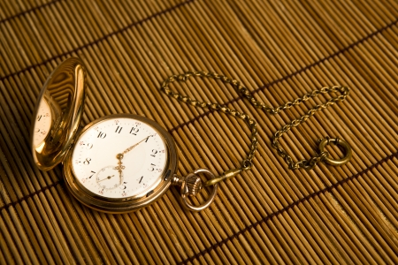 dispositions: Gold pocket watch on bamboo rugs close-up