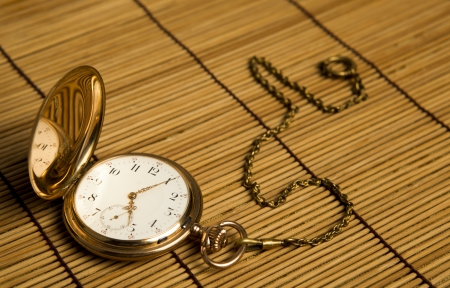 dispositions: Reloj de bolsillo de oro sobre alfombras de bamb� close-up