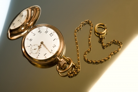 dispositions: Gold pocket watch on gold glass background close-up