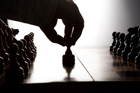 throwaway: silhouette hand of man making a move chess figure