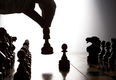 silhouette hand of man making a move chess figure