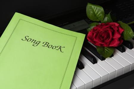 ピアノの鍵盤や歌の本、バラの花 写真素材