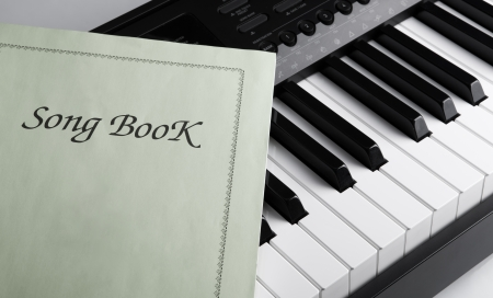 black and white keys of the piano closeup and song book photo
