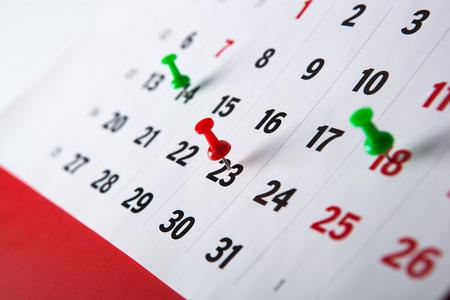 針のクローズ アップと壁掛けカレンダー カレンダー