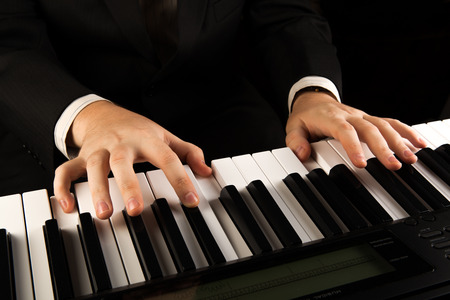 ピアノの鍵盤と人間の手のクローズ アップ