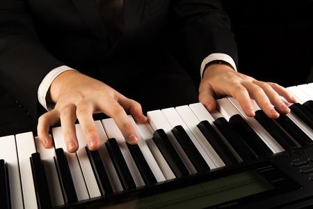 Piano keys and human hands close-up photo