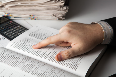 glossary: man is looking for information in the dictionary close-up