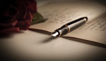 バラのクローズ アップとテキスト シート紙の上の万年筆