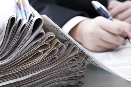 stack of newspapers in office close-up on white photo