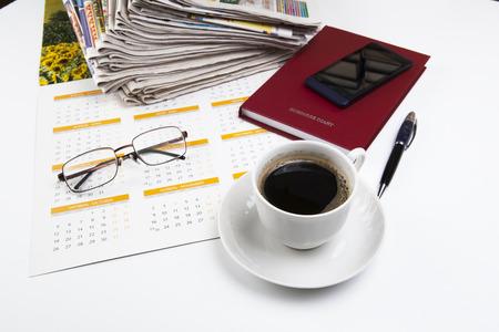 カレンダー、電話、日記、ペン、新聞、メガネのスタックのシートから成るビジネス静物 写真素材