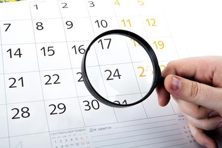 虫眼鏡を手に、白い背景で隔離の壁掛けカレンダー