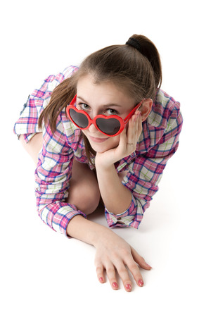 young girl in shorts and a t-shirt with red eyeglasses on a white background photo
