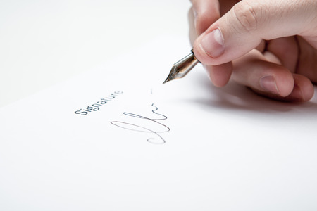 dispositions: pen in the mans hand and signature on a white