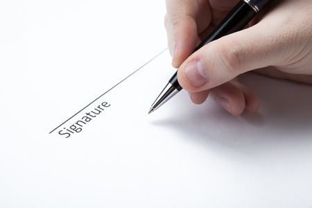 pen in the man's hand and signature on a white closeup Stock Photo - 27997158