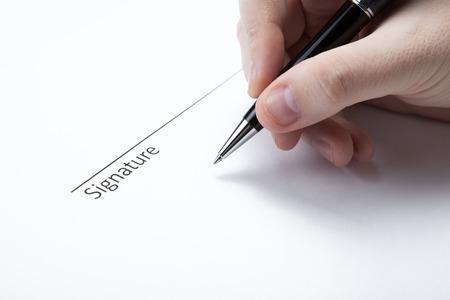 dispositions: pluma en la mano del hombre y la firma en un primer plano en blanco