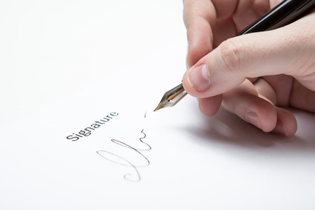 stipulation: pen in the mans hand and signature on a white closeup