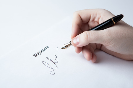 pen in the man's hand and signature on a white closeup Stock Photo - 27997166