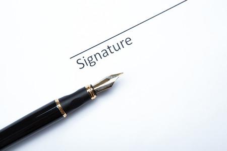 dispositions: pluma y firma en un primer plano en blanco