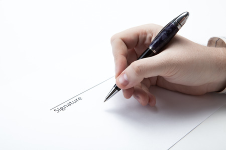 dispositions: pen in the mans hand and signature on a white closeup